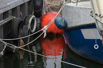 Oranje boei met reflectie in het water en detail van een vissersboot vastgebonden aan de kade in de  van Maren Winter