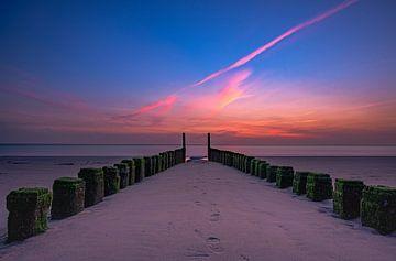 zonsondergang tussen een golfbreker. van Dirk Keij-Bron