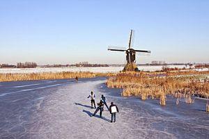 Schaatsen bij de molen op het platteland in Nederland van