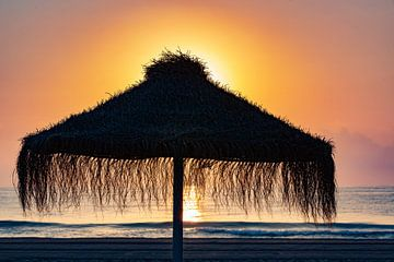 Parasol op het strand in de zonsondergang