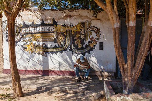 Straattafreel in Nazca, Peru. Lezende man onder de bomen voor een muurschildering