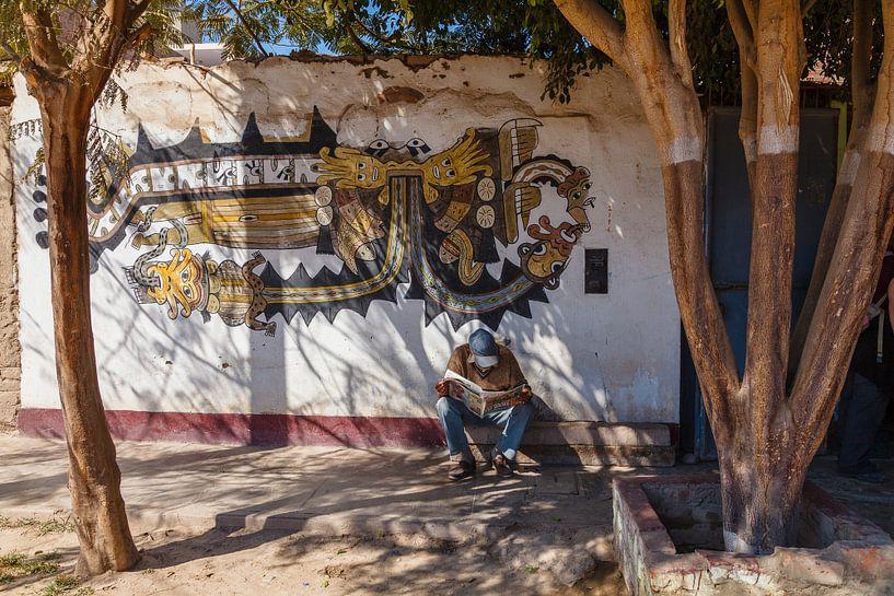 Straattafreel in Nazca, Peru. Lezende man onder de bomen voor een muurschildering van Martin Stevens