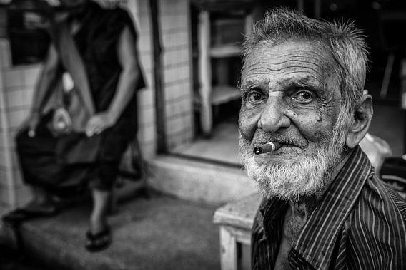 Oude getekende man rookt een cheroot sigaar in de straten van Yangon