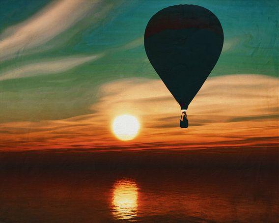 Een heteluchtballon zweeft over de zee tijdens zonsondergang