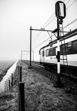 Een typische Nederlandse trein komt uit de mist en passeert een spoorwegsein van Hans Post