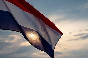 Nederlandse vlag tegen een ondergaande zon. van Femke Ketelaar