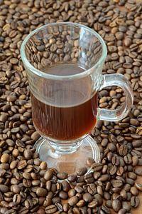 geröstete Kaffeebohnen und eine Tasse mit Kaffee von Heiko Kueverling
