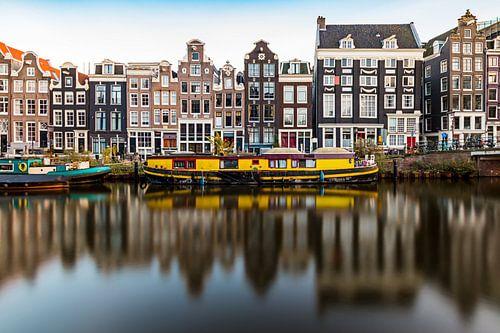 Amsterdam, reflectie, gracht, gele woonboot en grachtenpanden van