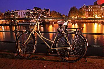 Oude fiets aan de Amstel in Amsterdam bij avond van Nisangha Masselink