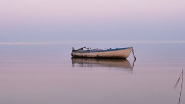 Eine romantische Aussicht: ein Boot auf dem See bei einem wunderschönen Sonnenuntergang von Ralph Rozema