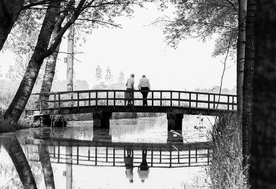 A lovely walk in the forest. Een ouder echtpaar op een brug in het bos in zwart wit