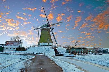 Middeleeuwse molen op het platteland in Nederland in de winter bij zonsondergang van Nisangha Masselink