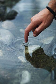 Le bout du doigt touche la surface de l'eau sur Besa Art