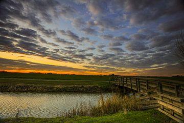 Bruggetje over het kanaal, met zon opkomst. van Henk Cruiming