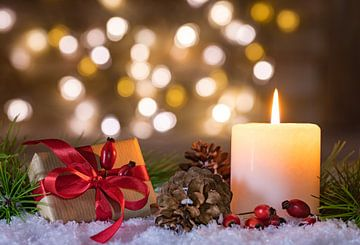 Kerstcadeau en kaars met natuurlijke decoratie van Alex Winter