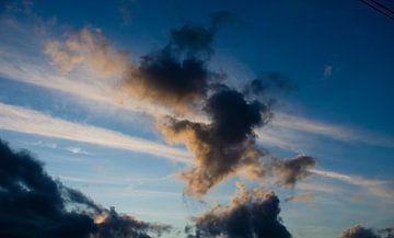 Blauwe hemel met donkere wolken. van Kim De Sutter