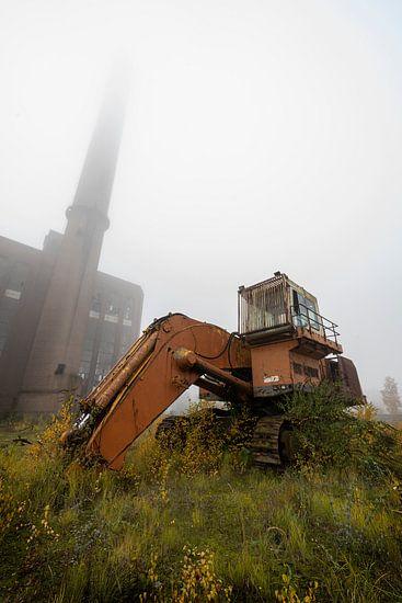 Verlaten graafmachine en fabriek met mist