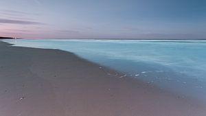 Strand en lichtblauwe zee onder een paarse hemel van