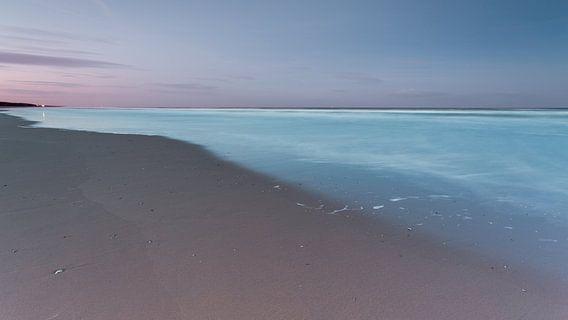 Strand en lichtblauwe zee onder een paarse hemel
