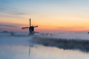 Sfeervolle zonsopkomst met molen en laaghangende mist