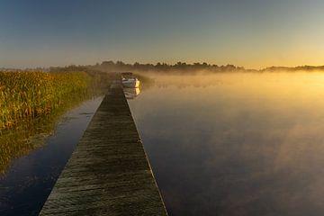 Lever de soleil sur un lac avec de la rosée et un bateau amarré à une jetée dans le parc national de sur Dafne Vos