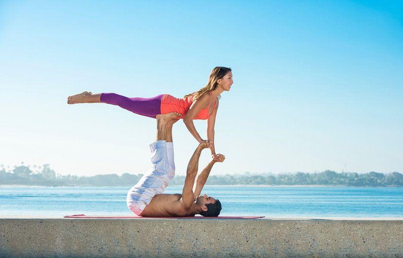 Man en vrouw in akrobatische yoga positie op het strand in San Diego van BeeldigBeeld Food & Lifestyle