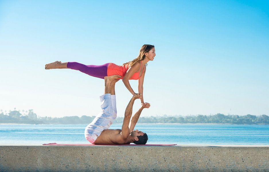 Man en vrouw in akrobatische yoga positie op het strand in San Diego van Beeldig Beeld
