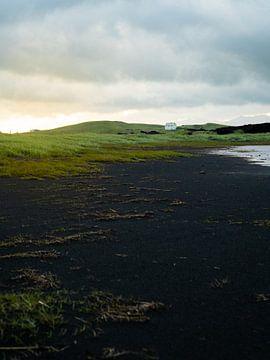 Kleines weißes Haus und schwarzer Strand in Island von Teun Janssen