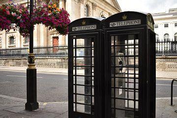 Cabines téléphoniques noires Londres à côté de fleurs suspendues sur Mireille Schipper