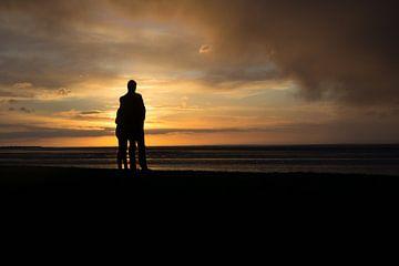 Romantisch jong stel bij ondergaande zon aan de Waddenzee van Tim Groeneveld