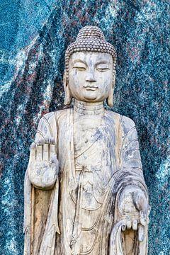 Boeddhabeeld voor een blauwe granieten muur van