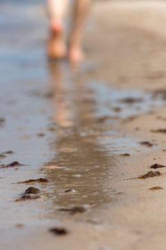 Frau geht am Meeresstrand entlang mit unscharfen Bereichen von
