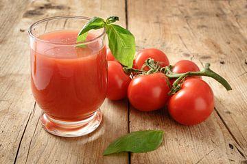 frischer Bio-Tomatensaft im Trinkglas mit Pfeffer und Basilikum garniert auf einem rustikalen Holzbr von Maren Winter