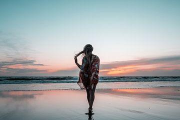 Vrouw maakt strand wandeling tijdens zonsondergang