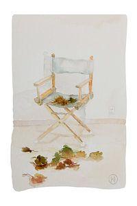 Regisseursstoel met herfstbladeren van