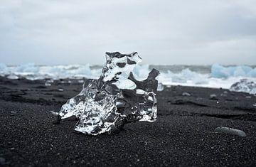 Kristalhelder ijsrots op zwarte sand bij ijsmeer Jokulsarlon, Ijsland van Jutta Klassen