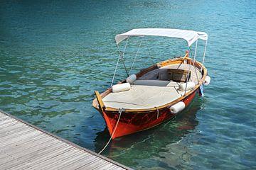 Rode houten boot met ligvlak en zonnescherm op de steiger in het turquoise water van de Middellandse van Maren Winter