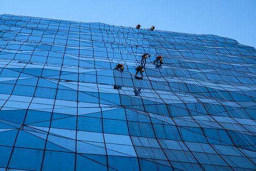Glazenwassers op eenzame hoogte op glazen gevel