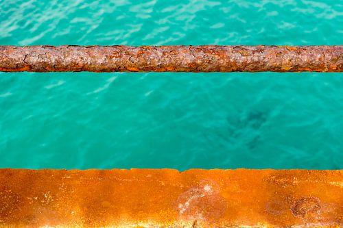 Turquoise water en een roestige kade van