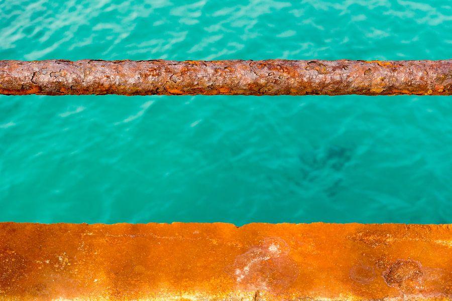 Turquoise water en een roestige kade van Michel van Kooten