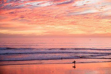 Surfer bij zonsondergang in Taghazout, Marokko