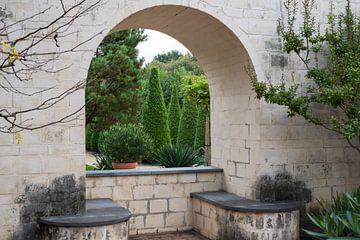 doorkijkje door muur en boog naar tuin von Compuinfoto .