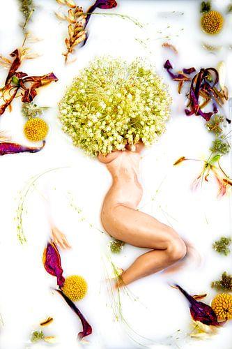 Naakte vrouw in melkbad met bloemen