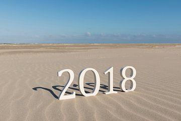 Tekst tweeduizend achttien op een strand von Tonko Oosterink