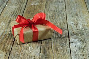 Einzelne Geschenkbox mit roter Schleife auf Holz von Alex Winter