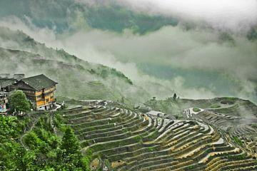 huis op de heuvel is een heuvel van wolken en mist. Mistig herfstlandschap met rijstterrassen. China van Michael Semenov