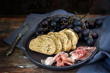 frisches Vollkornbrot mit blauen Trauben und Prosciuttoschinken auf einem dunklen rustikalen Holztis von Maren Winter