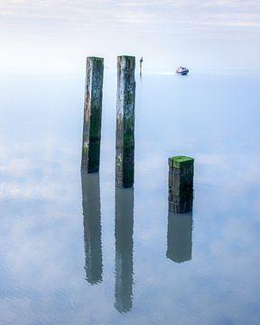 Poteaux de balisage sur la jetée de Holwerd par une journée sans vent sur Harrie Muis