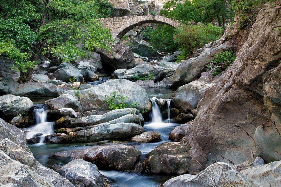 Een rivier in de kloof tussen twee bergen met een oude stenen brug