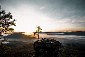 Landschap met mist, rotsen en kruis in zonsopgang van Fotos by Jan Wehnert